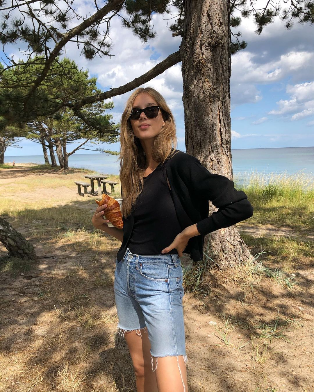 Sacnidnavian Spring Outfit Summer outfit Idea —Cecilie Moosgaard Nielsen in a black tank top, cardigan and long jean shorts