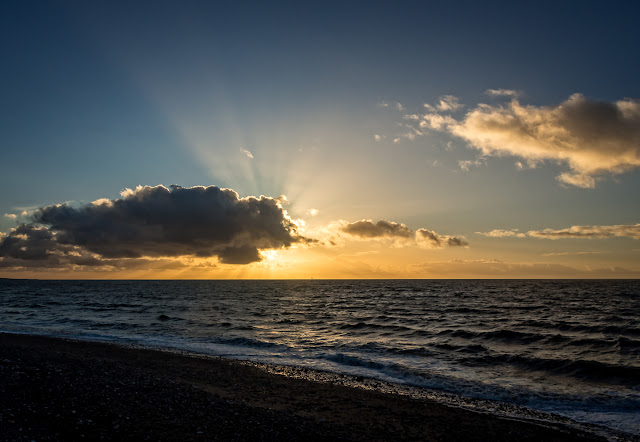 Photo of the sun setting behind clouds over the Solway Firth in Cumbria