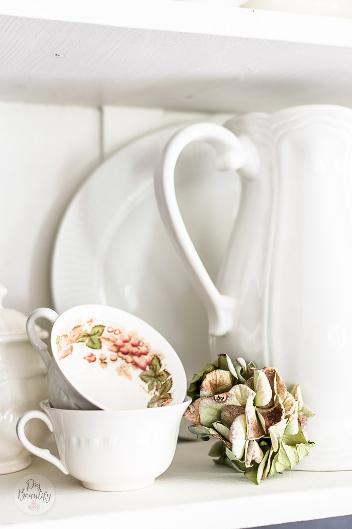 white ironstone pitcher, vintage teacups and dried hydrangea stem