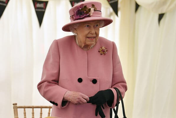 Queen Elizabeth wore a pink coat by Stewart Parvin and matching hat by Rachel Trevor-Morgan. Carved Ruby, gold and diamond brooch, Grima ruby brooch