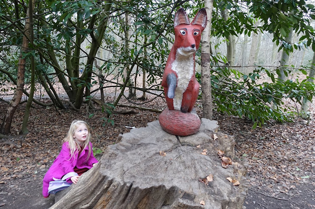 A girl creeping up on a wooden carving of a fox at the Gruffalos trail essex