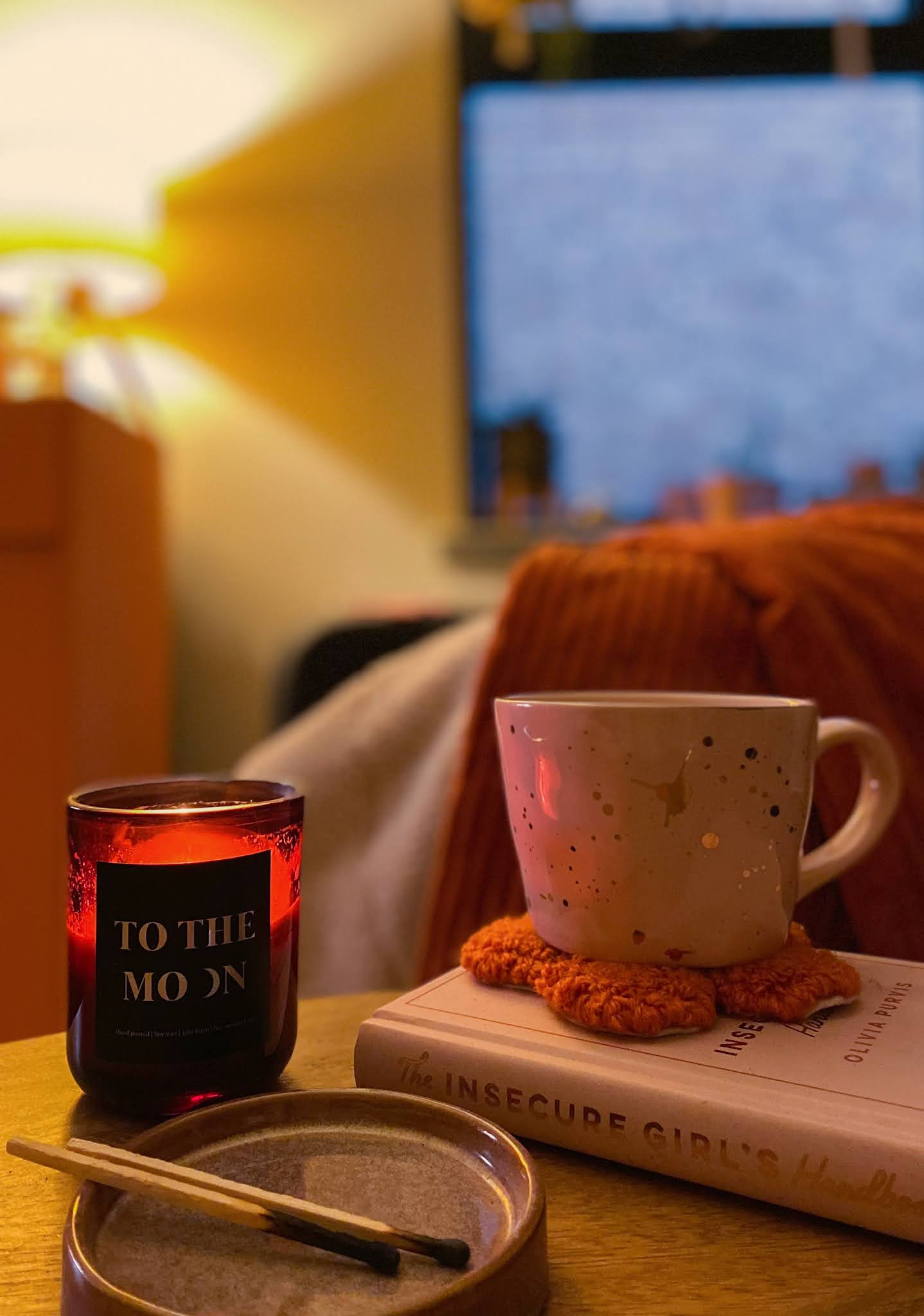 cosy autumn living room with cup of tea, book and a candle
