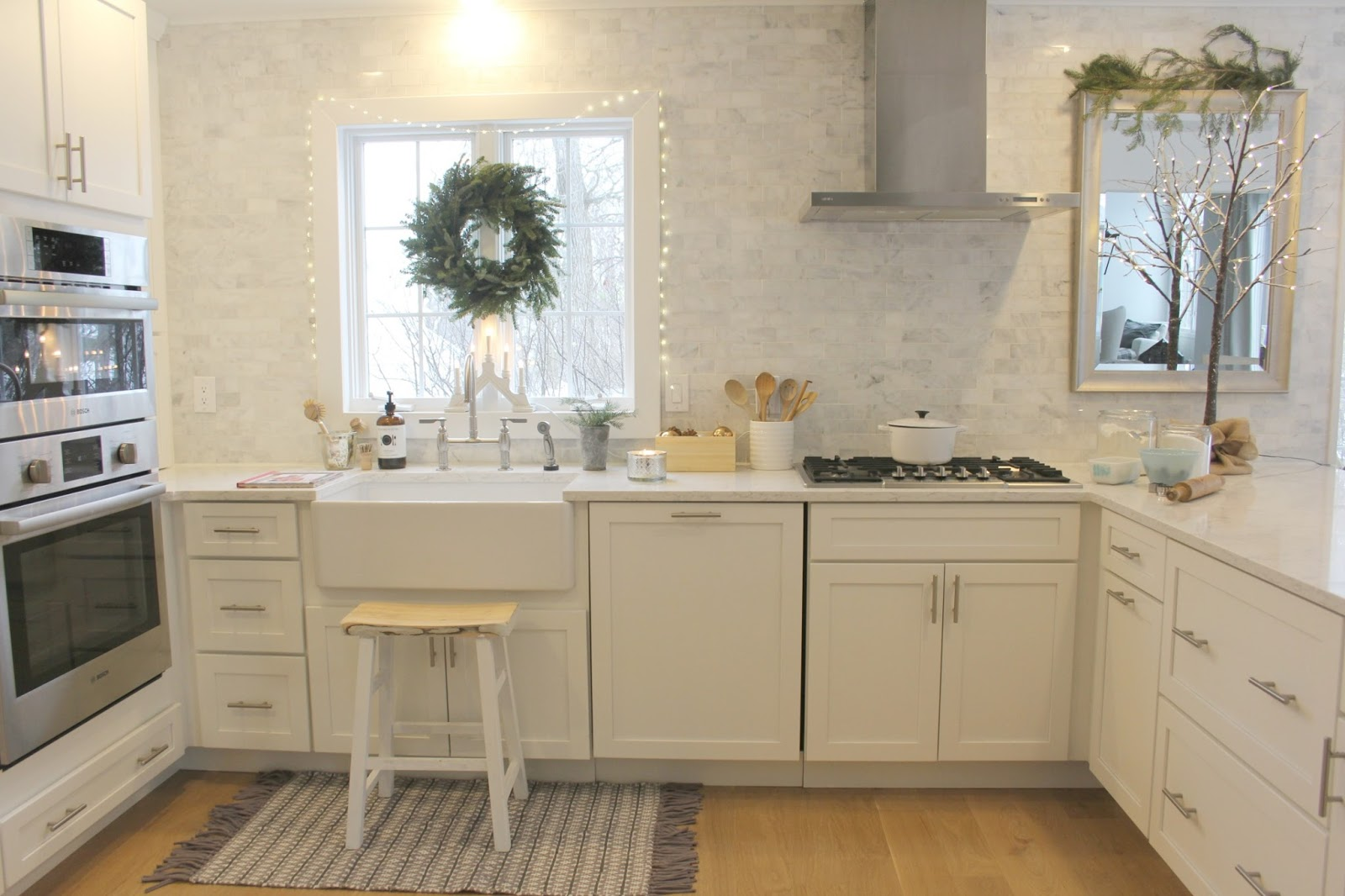 Holiday decorated white modern farmhouse kitchen with marble subway tile