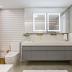 Banheiro com banheira branco e cinza com metais dourados e cuba dupla!