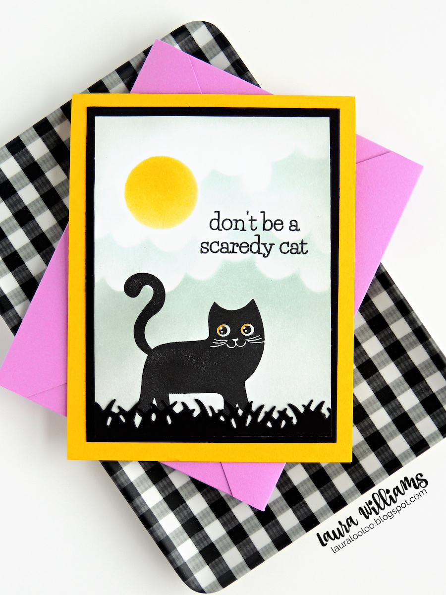 """This image is a handmade Halloween card with a stamped cat in black ink. The cat is standing in black grass under a cloudy moonlit sky, created with inking and handmade stencils. The sentiment says """"Don't be a scaredy cat."""" The card is resting on a purple envelope and a black & white gingham tray."""