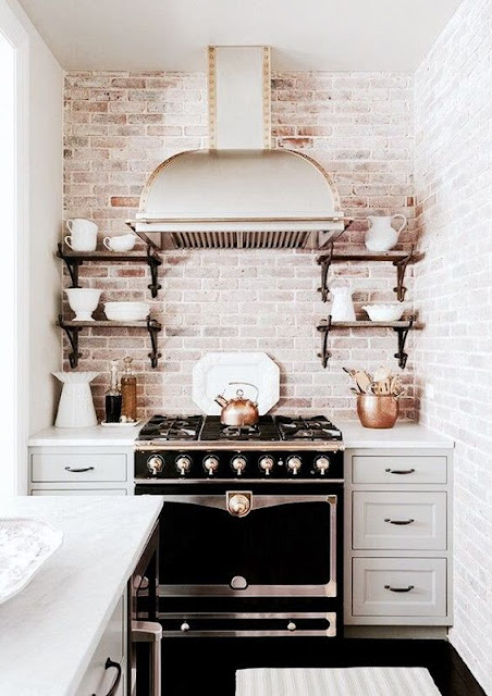 brick white washed wall, black stove, chrome hood and grey cabinets