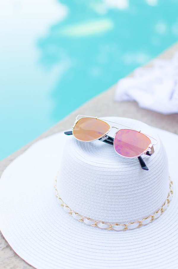 Pink tinted sunglasses on top of a white sunhat by the pool