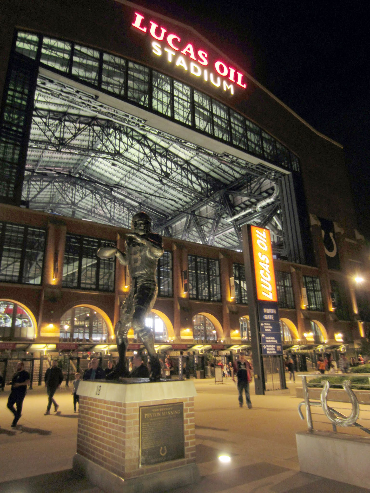 Lucas Oil Stadium exterior and Peyton Manning statue at night