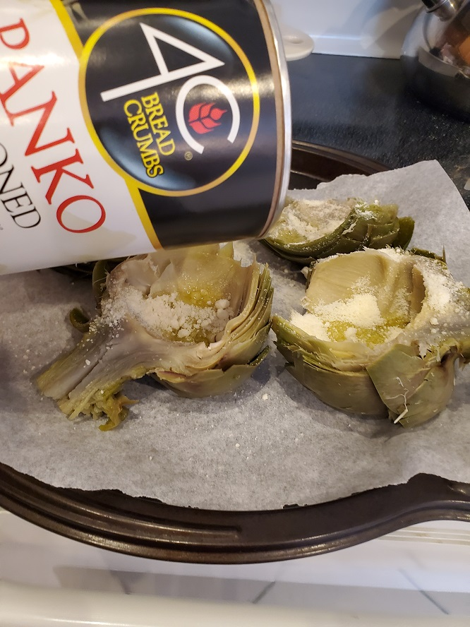 this is the recipes for how to make stuffed grilled artichokes on a cookie sheet getting stuffed with bread crumbs