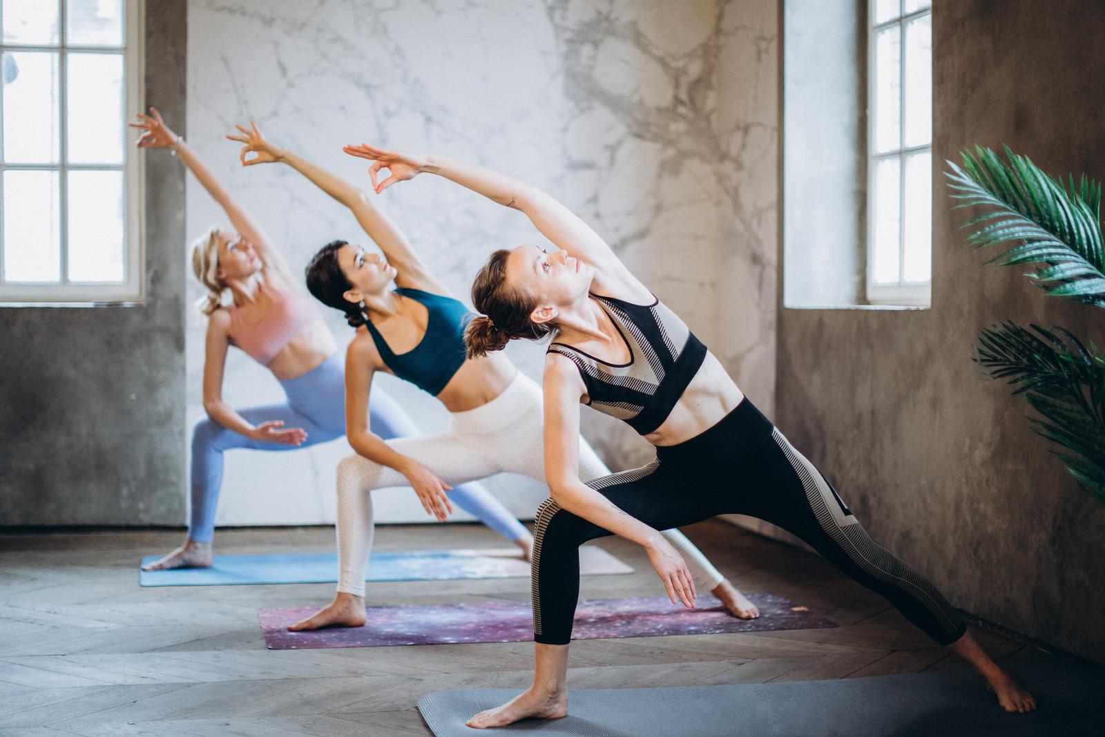 three women in same yoga pose