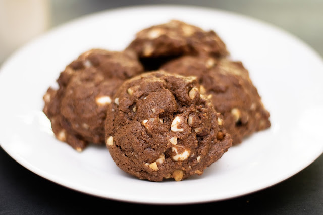 The finished triple chocolate macadamia nut cookies on a white plate.