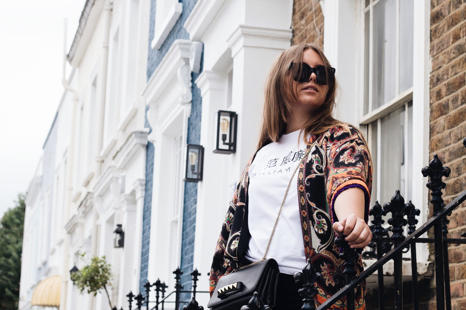 fashion blogger dominique candido wearing etro jacket poncho, celine tilda sunglasses, william fan t shirt, citizens of humanity jeans, valentino va va voom bag and balenciaga speed runners