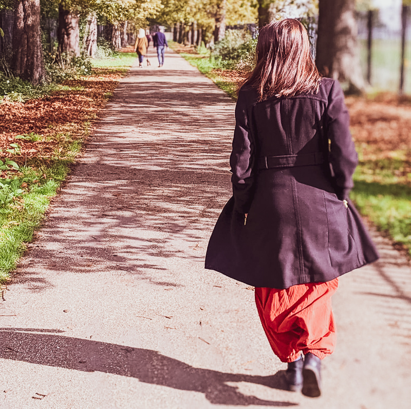 Brunette woman walking down a tree lined path with her back to the camera wearing a black coat with an orange jumpsuit underneath