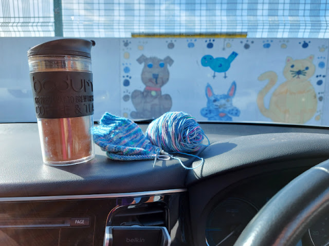 A travel mug of tea, a half-knitted sock and a ball of yarn are on a car dashboard.  Out of the window is a large picture of pets drawn by a child