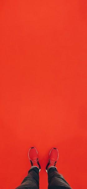 خلفية شخص يرتدي حذاء أحمر على أرضية حمراء