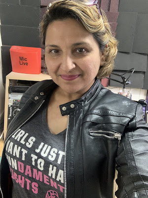 Woman in leather jacket in radio studio looking into camera