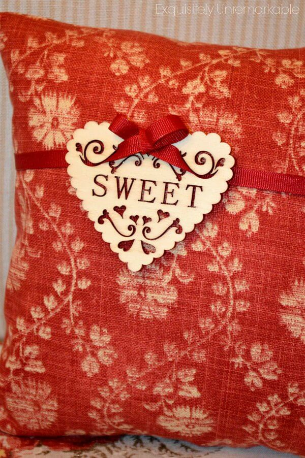 Red pillow with wooden heart that says SWEET attached with ribbon