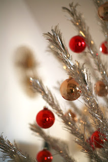 Closeup of red and gold ornaments on a silver aluminum tree.