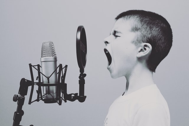 Boy screaming into microphone in black and white