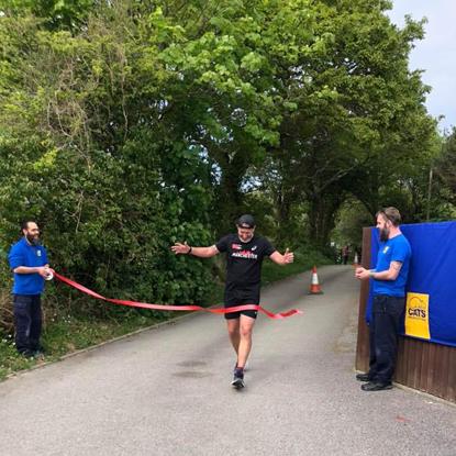 Man running through finish line ribbon at Cats Protection centre