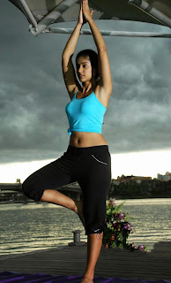Ileana doing yoga in a blue tank top and black yoga pants