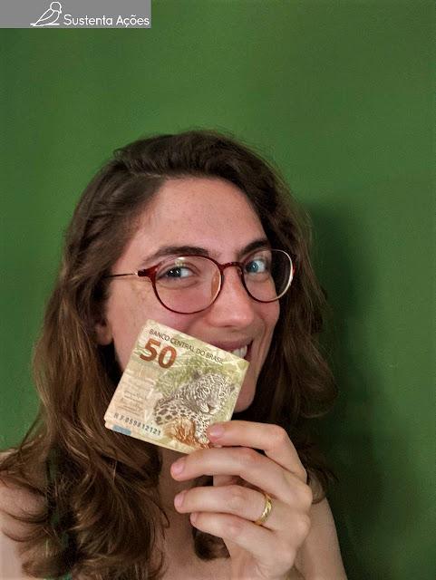 Letícia segurando uma nota de 50 reais