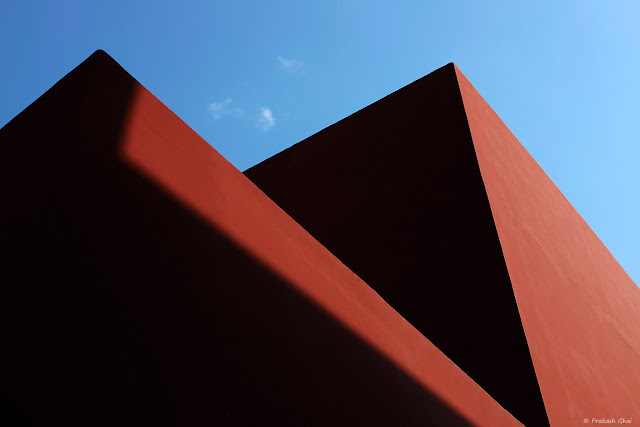 A Looking Up Minimalist Photograph of Shadows on the Red Walls of Jawahar Kala Kendra, Jaipur.