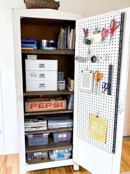 Open door craft cabinet with pegboard door.