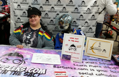 A woman sitting at a pop culture convention table.
