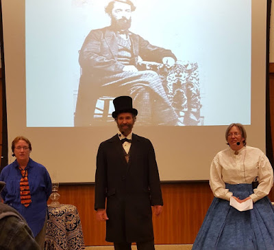 Curator and reenactors in front of historic photo of Edwin Drake