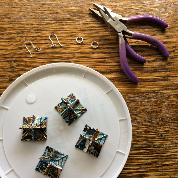 folded paper earring components glued and drying on plastic lid alongside jewelry pliers and silver earring findings