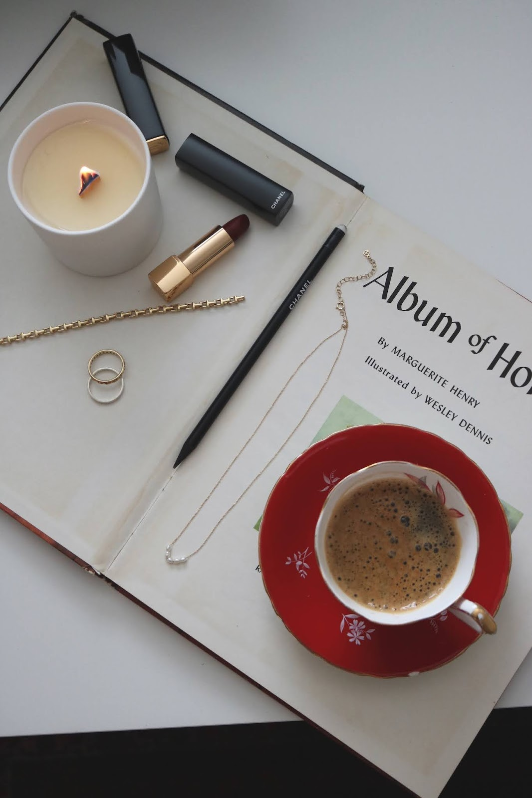 Chanel makeup rests on a book with coffee