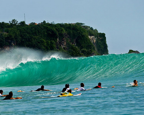 Tinuku.com Travel Surfing Uluwatu beach riding 8 meters Indian Ocean waves in hidden spots under sacred temple cliffs