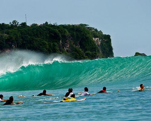 Tinuku.com Travel Surfing Uluwatu beach riding 8 meters Indian Ocean waves in hidden spots under sacred temple cliffs