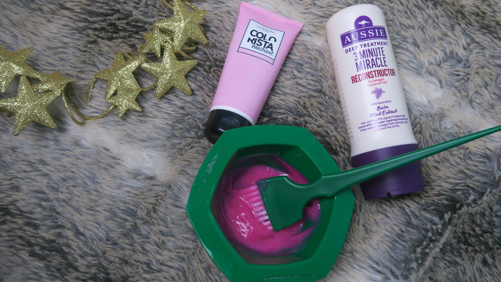 aussie three minute miracle reconstructor, alongside a green dye bowl and brush, with an intense pink cream solution in the bowl, on a faux fur throw; a teal cushion and gold star wreath sit beside them, along with l'oreal colorista washout pink hair dye