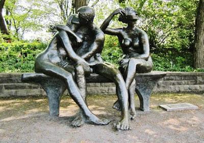 Estátuas de um homem e uma mulher sentados num banco se beijando, enquanto outra estátua de mulher permanece ao lado descontente