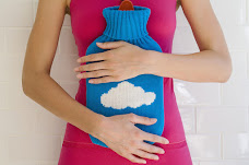 A women wear a pink dress holding a hot water bottle to her stomach. The hot water bottle is blue cover with a cloud design on it.