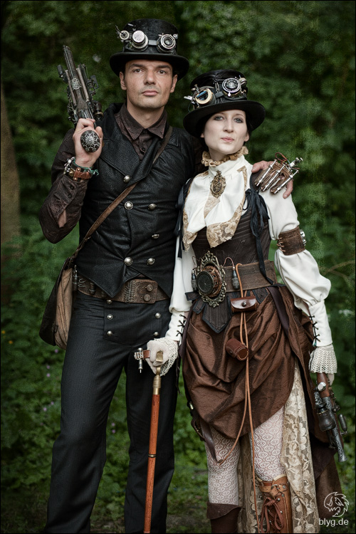 Men and women's steampunk clothing. Man wearing a vest, top hat, goggles and gun. Woman wearing a victorian blouse, corset, skirt, belt, top hat and goggles.