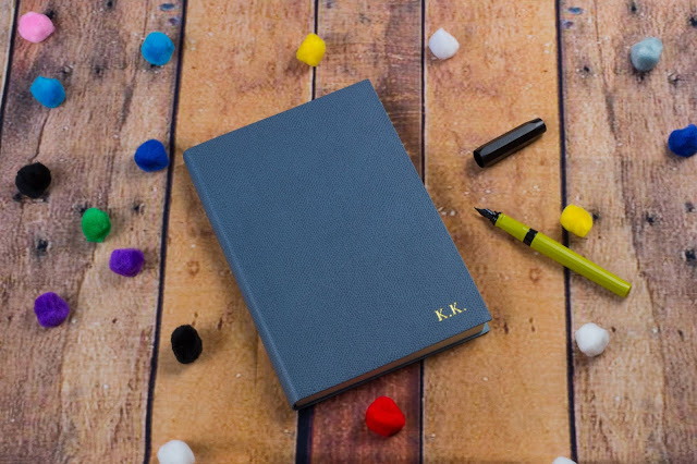 A beautiful leather journal with gold embossed letters saying KK on floor boards next to an open fountain pen