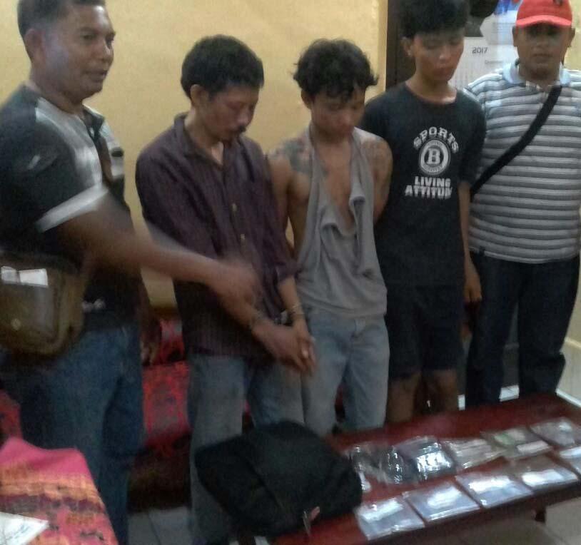 Ketiga tersangka narkoba saat berada di kantor polisi bersama barang bukti.