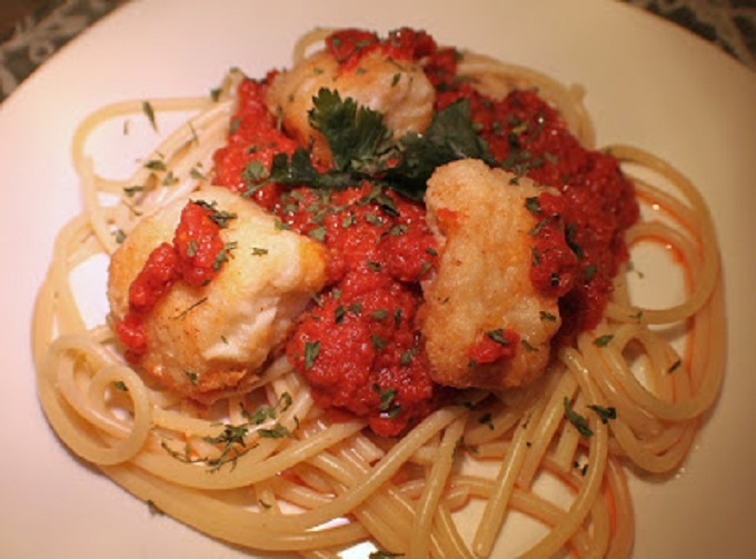 Baccalà, or salted codfish is a plate of pasta topped with marinara sauce and fried salted cod fish called baccala