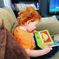 A redheaded toddler reading a book