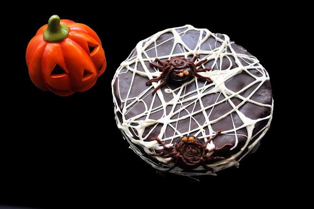 una tarta cubierta de telañaras con dos arañas hechas de oreos