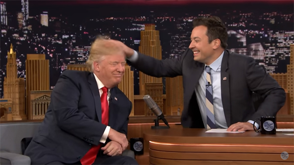 screen shot of Jimmy Fallon ruffling Donald Trump's hair, while they both smile