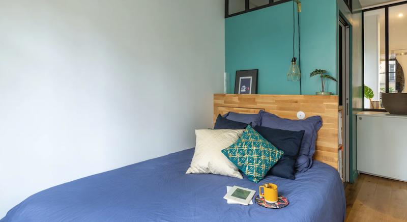 Dormitorio doble con cabecero pintado de verde aceituna
