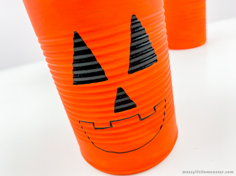 Drawing face on tin can Jack O Lantern