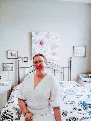 Sarah is sat on her bed in a white dress looking at the camera and smiling