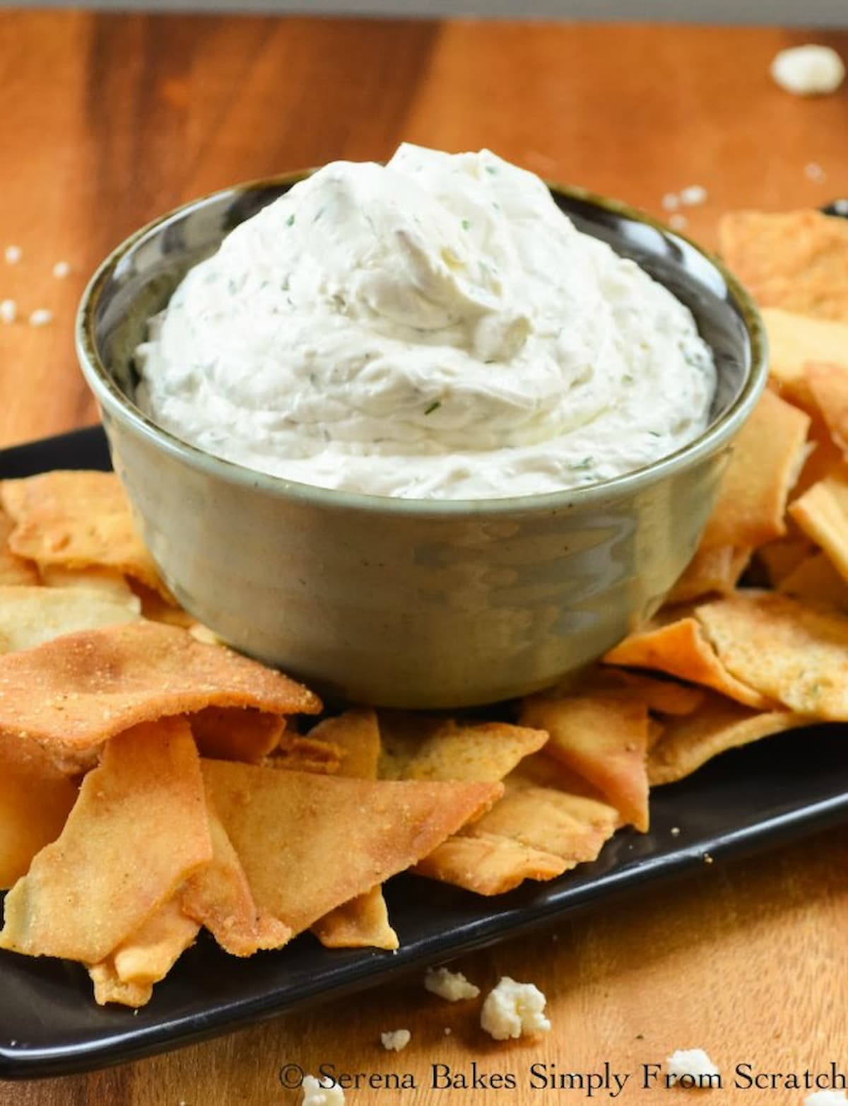 Greek Feta Dip in a small bowl with pita chips spread around the edge.