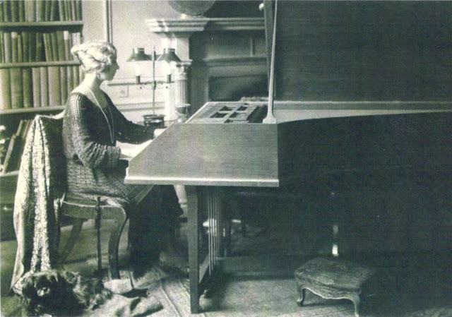 Violet Gordon-Woodhouse in the drawing room of Nether Lypiatt Manor, playing her Dolmetsch harpsichord