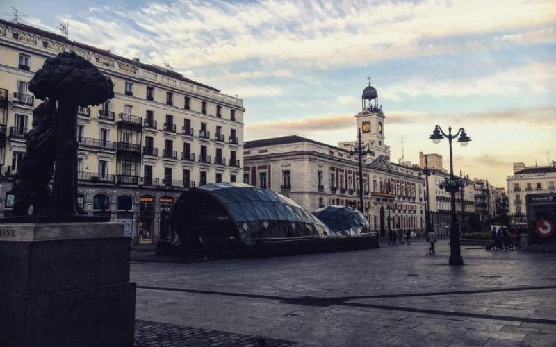 Amanecer de otoño en la Puerta del Sol, con el oso y el madroño